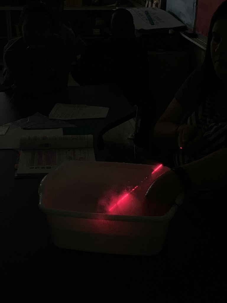Using a fog machine to show how light travels in a straight line.