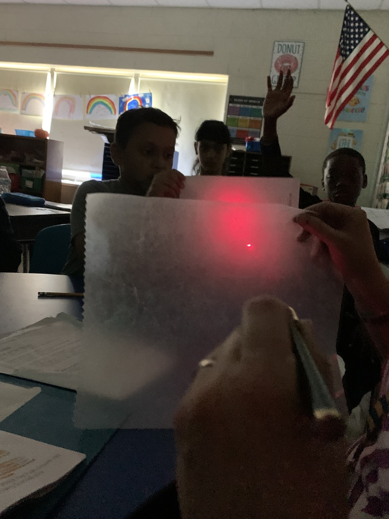 Showing how light is dispersed differently through wax paper and is able to travel through to reach the paper.